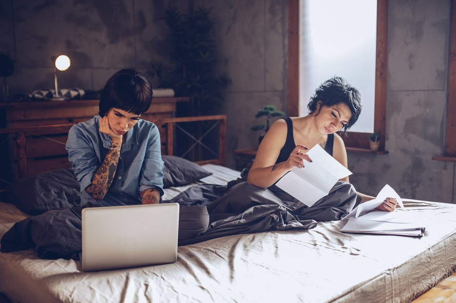 two females seated on a bed looking through documents and on a laptop