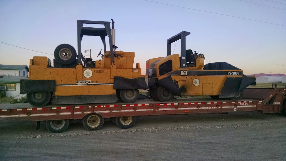 two caterpillar rollers loaded on a flatbed trailer