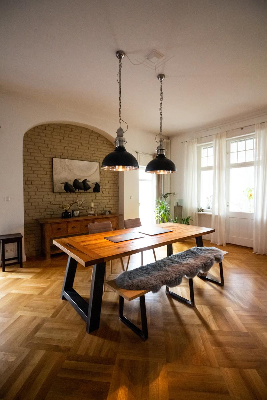 Big light fixtures atop a roomy dining room