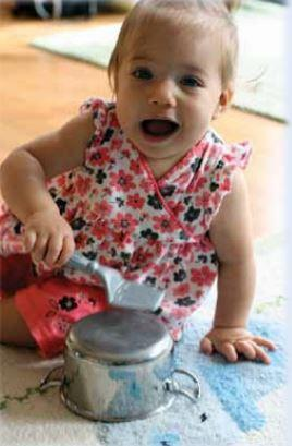 An infant hitting a metal pot with a spatula