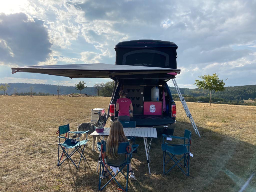 Kinder sind am Dachzelt Mobil und beschäftigen sich