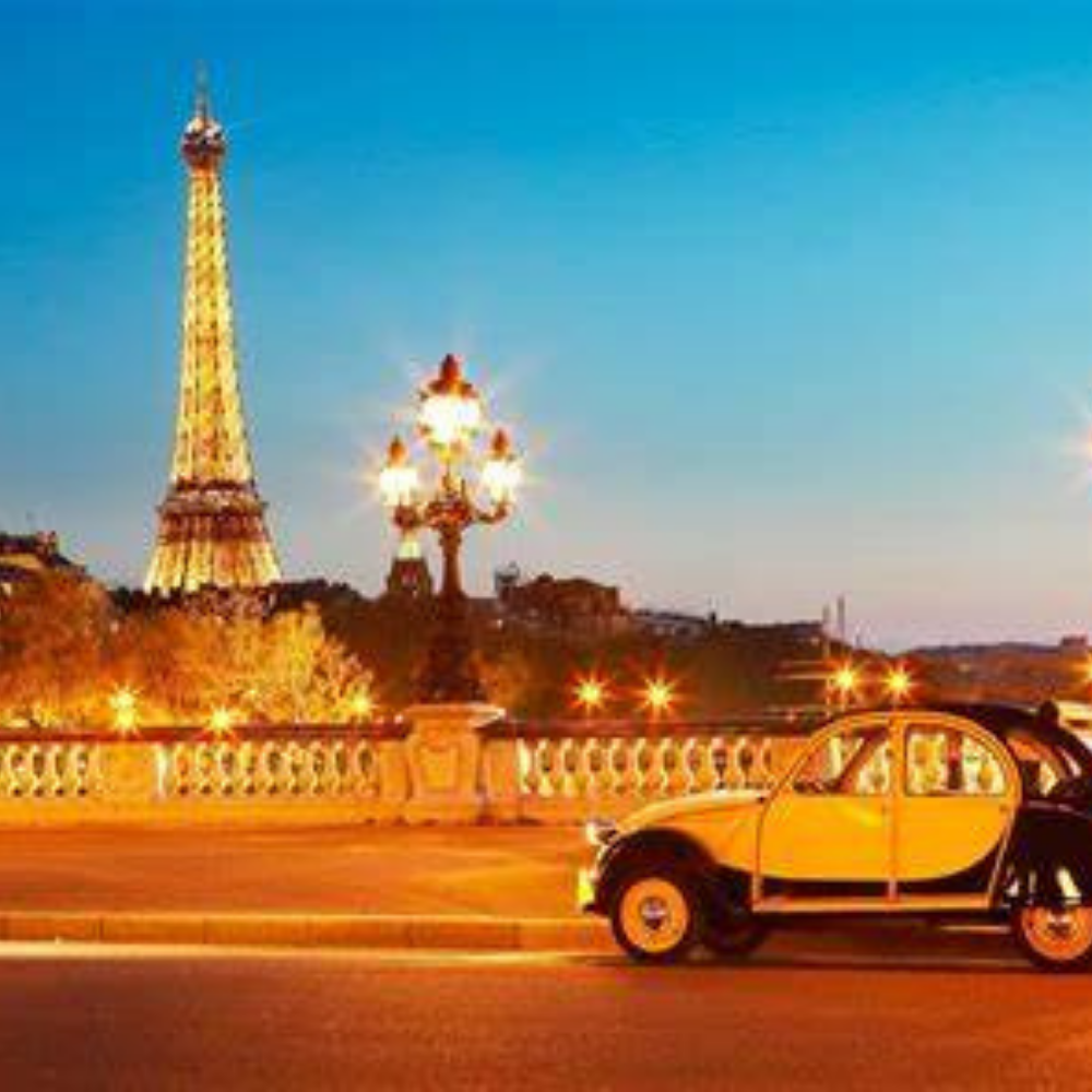 A vintage car driving by the Eiffel Tower