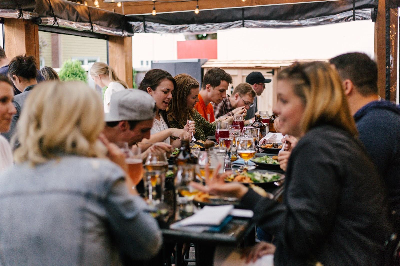 Várias pessoas comendo e conversando em uma longa mesa.
