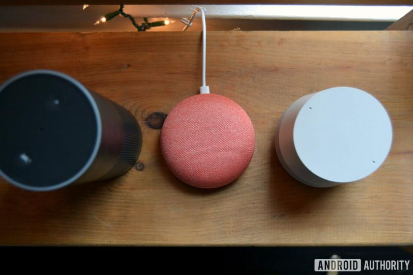 Amazon Echo, Google Home Mini, and Google Home top-down image on wood table.