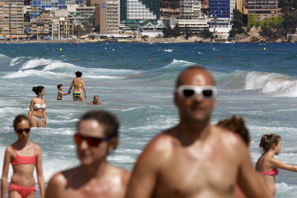 A photo of holidaymakers walking along a beach and swimming in the sea by Martin Parr