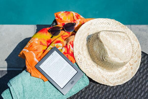 foto de um chapéu, óculos de sol, canga e kindle na beira da piscina
