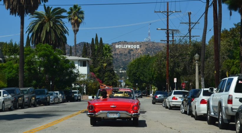 Convertible driving in Los Angeles with Hollywood sign