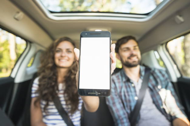 Mulher segurando celular sentada no banco de motorista ao lado do passageiro.