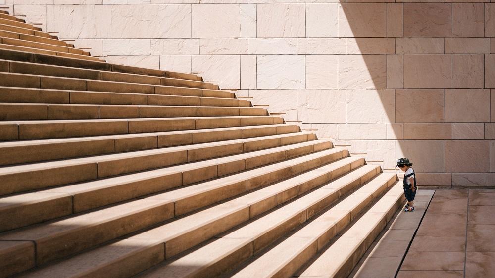niño pequeño de pie al pie de la gran escalera
