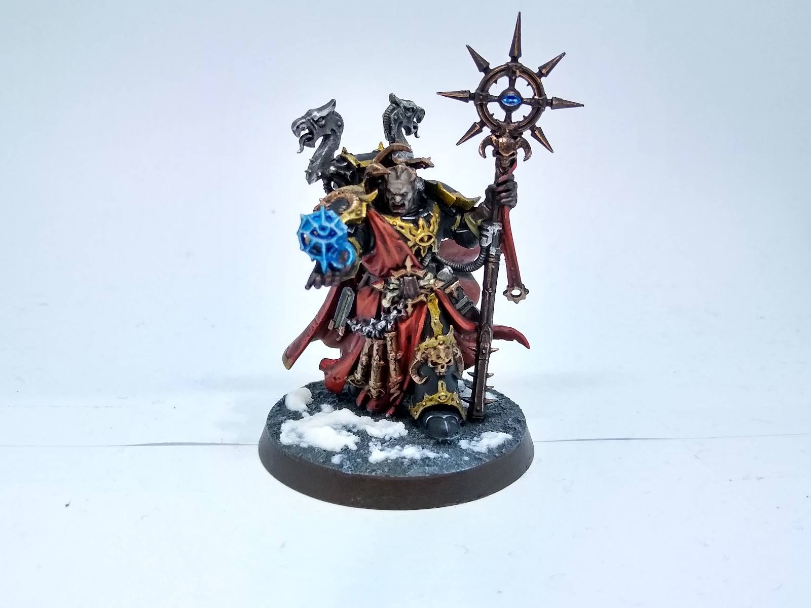 Model sorceror in black and gold armour and a red cloak, holding a staff and a glowing blue sigil.