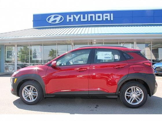 a red 2019 Kona Essential sits parked outside of Integrity Hyundai in Lethbridge