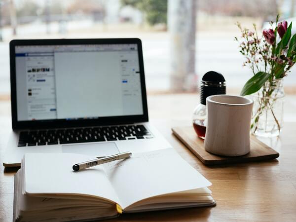 Foto de uma mesa com computador, agenda, caneca e flores.