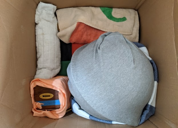Fragile items wrapped in towels and clothing to protect them during a long distance move.