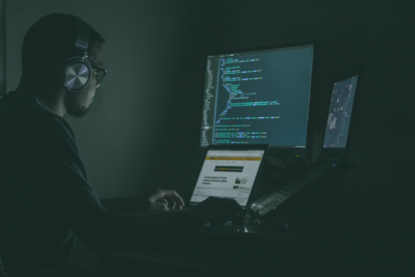 a person wearing headphones and coding on multiple computers