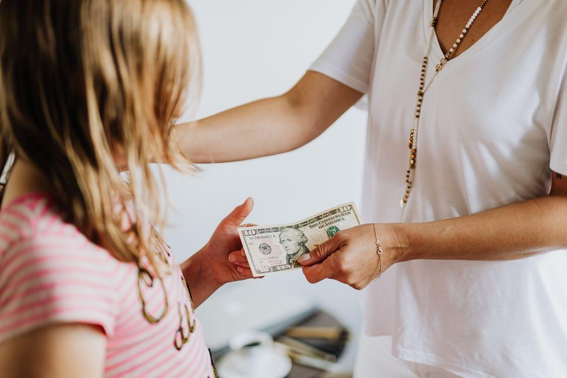 Woman Giving 10 Dollars to a Girl