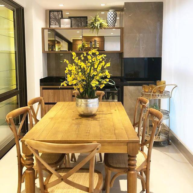área gourmet com churrasqueira revestida de porcelanato marmorizado nas cores preta e marrom puxado para a madeira. Com mesas e cadeiras de madeira, bancada de granito preto e piso de porcelanato neutro.