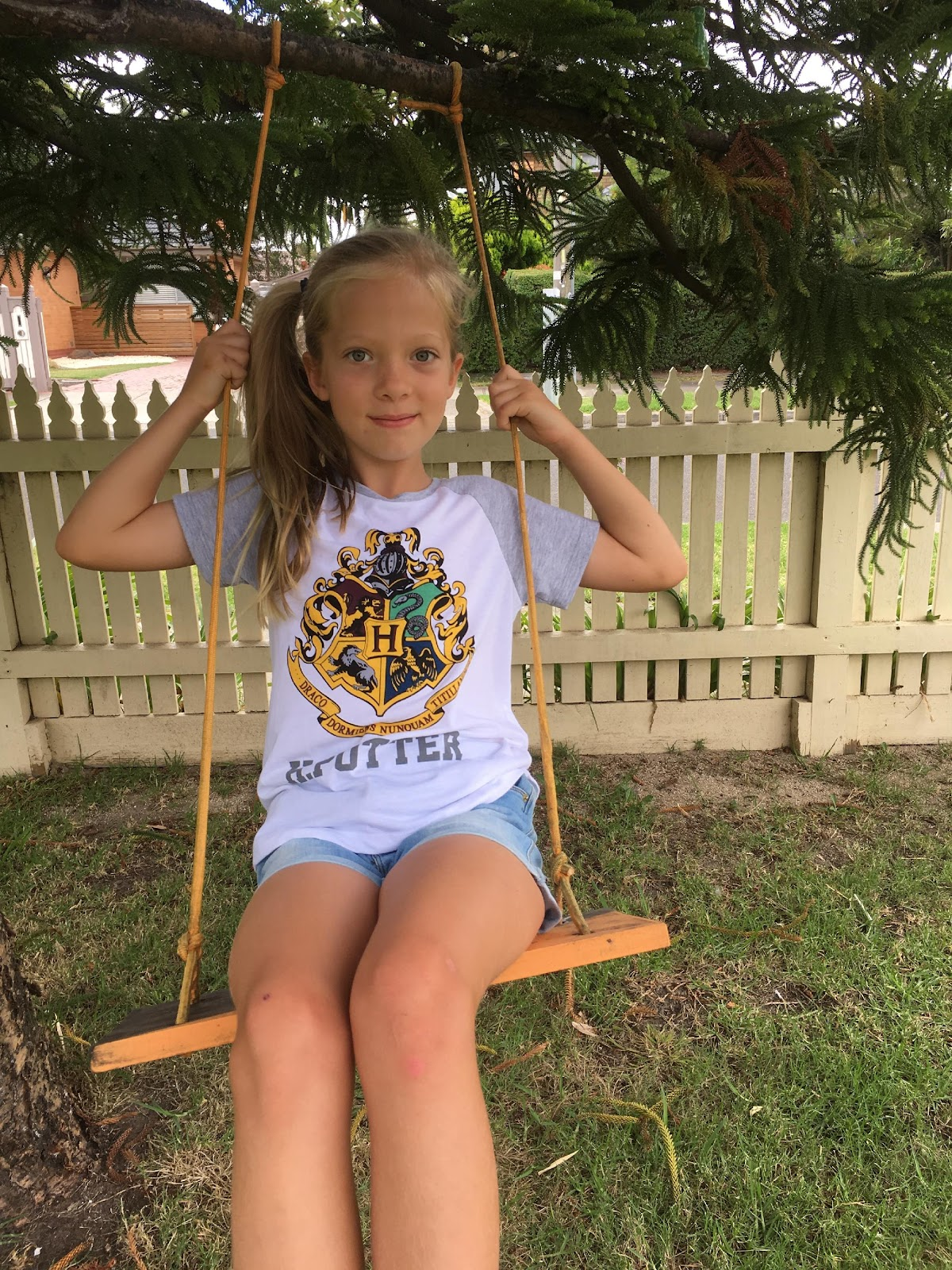 Girl wearing Harry Potter tshirt while sitting on a swing.