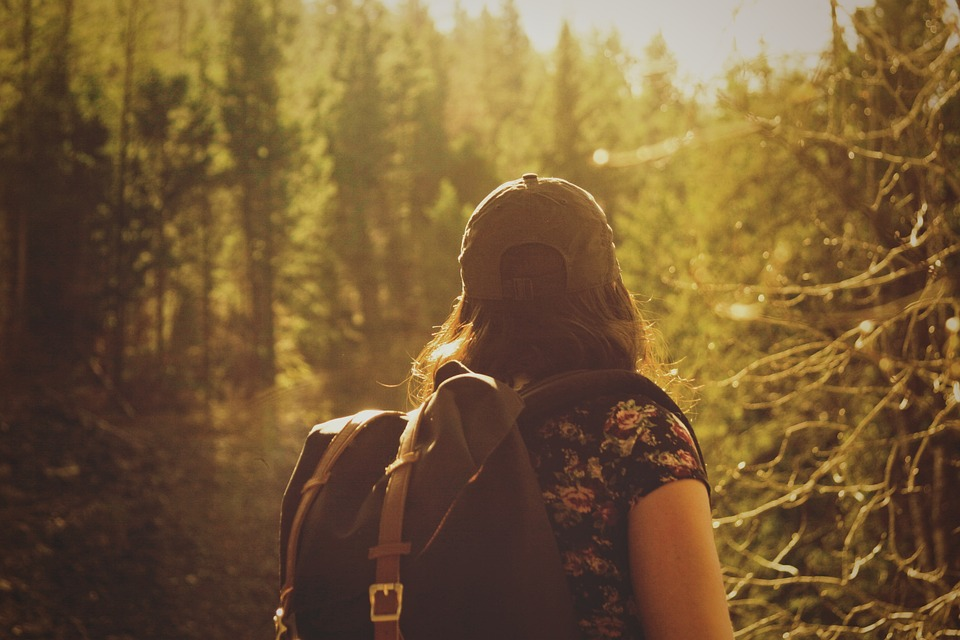 solo woman traveller with backpack in the woods