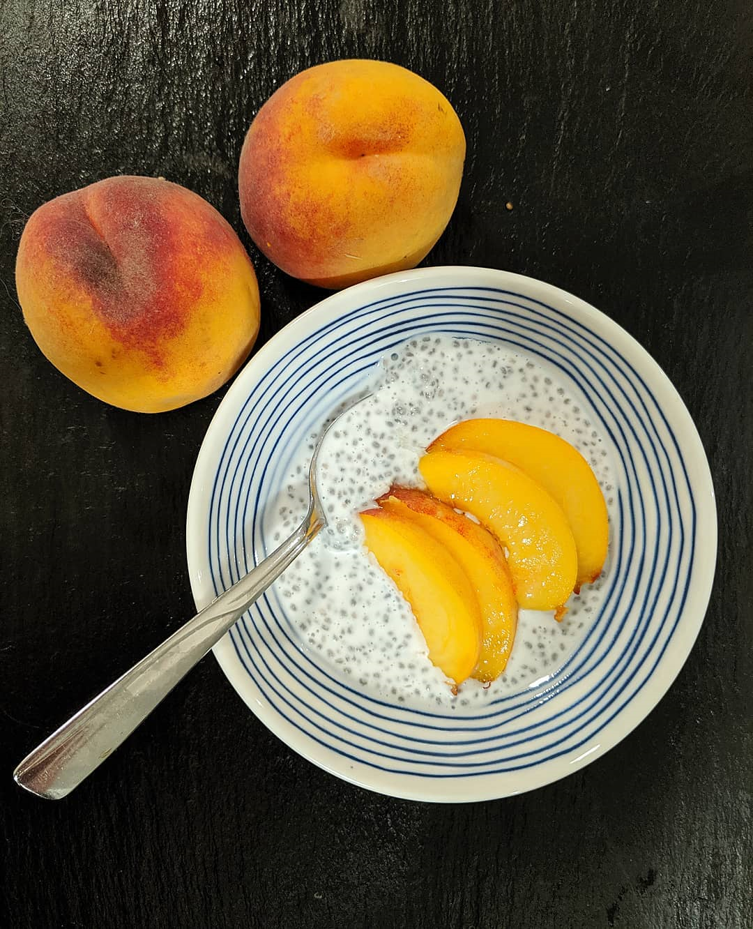 chia pudding with peaches in blue stripped bowl