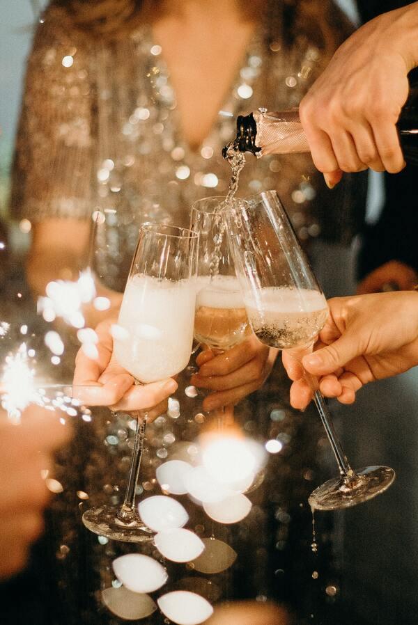 foto de alguém enchendo as taças com champanhe