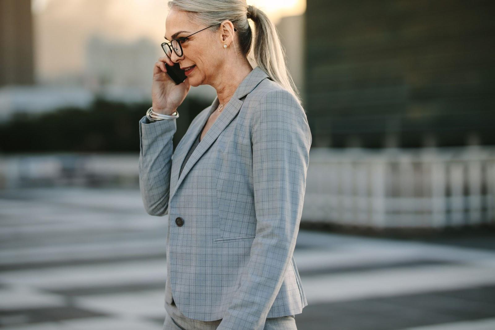 Foto de uma mulher de meia idade, vestida com roupas formais de trabalho, falando em seu celular, ilustrando a resolução de problemas por meio do teletrabalho e do remote everything