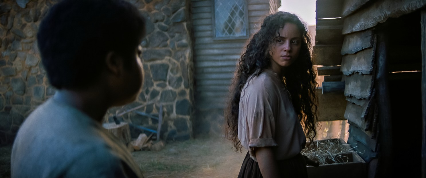 Still from Fear Street part 3. Deena sands outside a wooden house, wearing a blouse and skirt as her 1666 counterpart Sarah. She glances over her shoulder at an obscured figure watching her in the foreground.