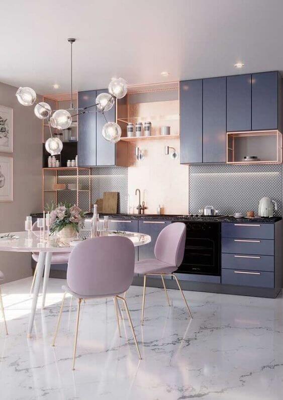 Cozinha com piso porcelanato reproduzindo mármore, armário azul com detalhes rosa, mesa branca redonda com cadeiras lilás e luminárias pendente de bolas transparentes.