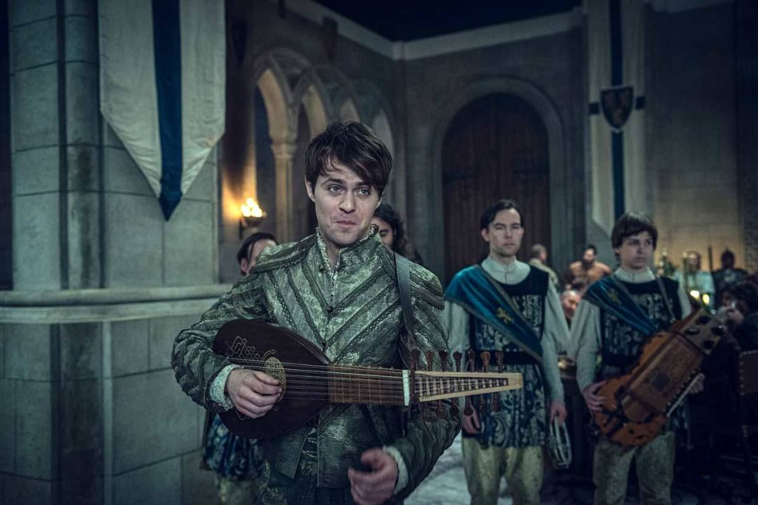 A bard is holding a small medieval guitar inside a castle.