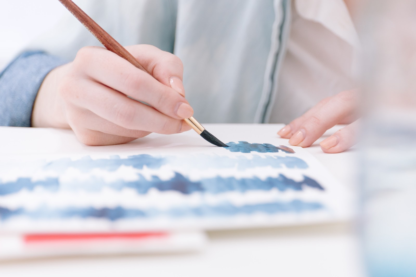 A person painting blue design