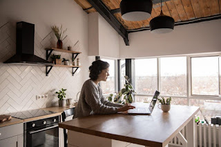 Side view of young female in casual clothes typing message on laptop while sitting at wooden table in kitchen