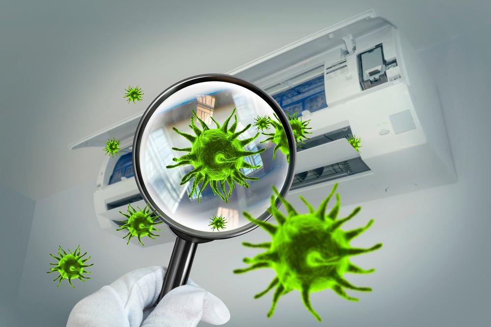 Uma lupa enxergando vírus em um ar condicionado.