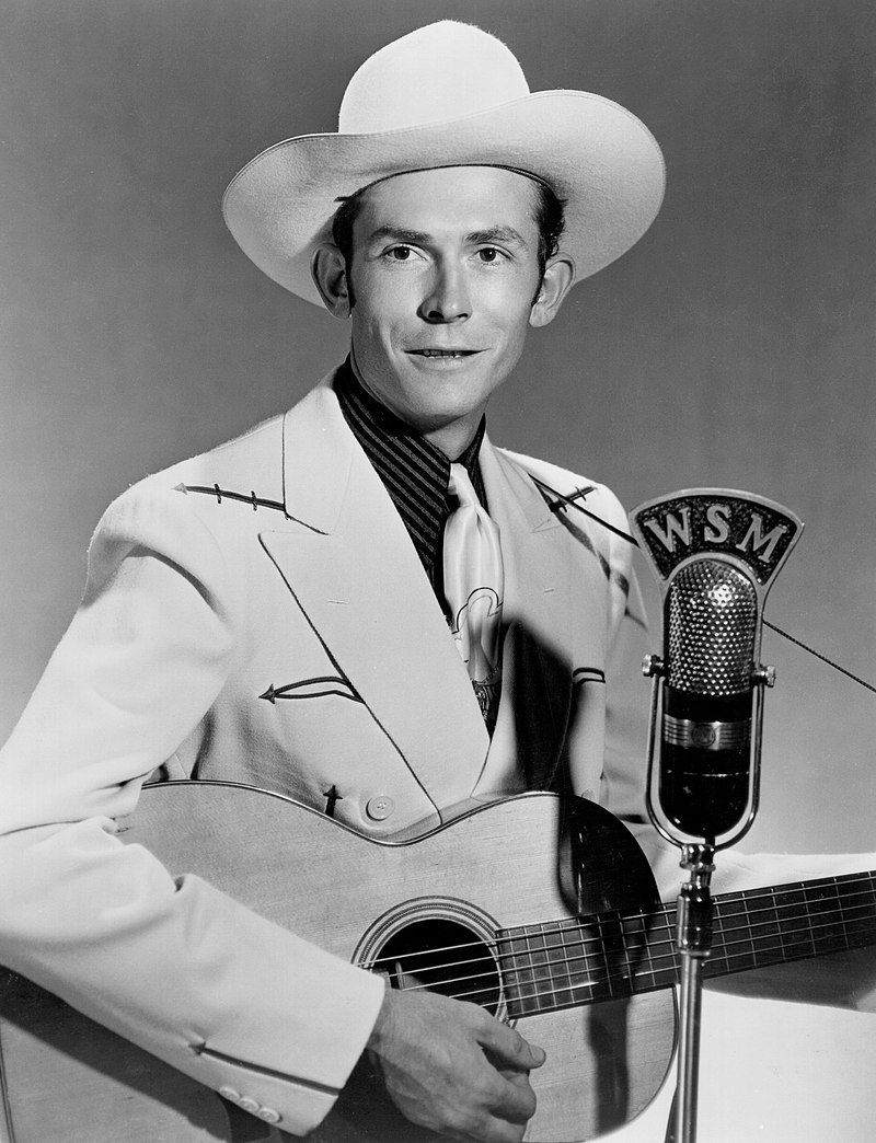 A picture of Hank Williams holding the guitar in front of a microphone.