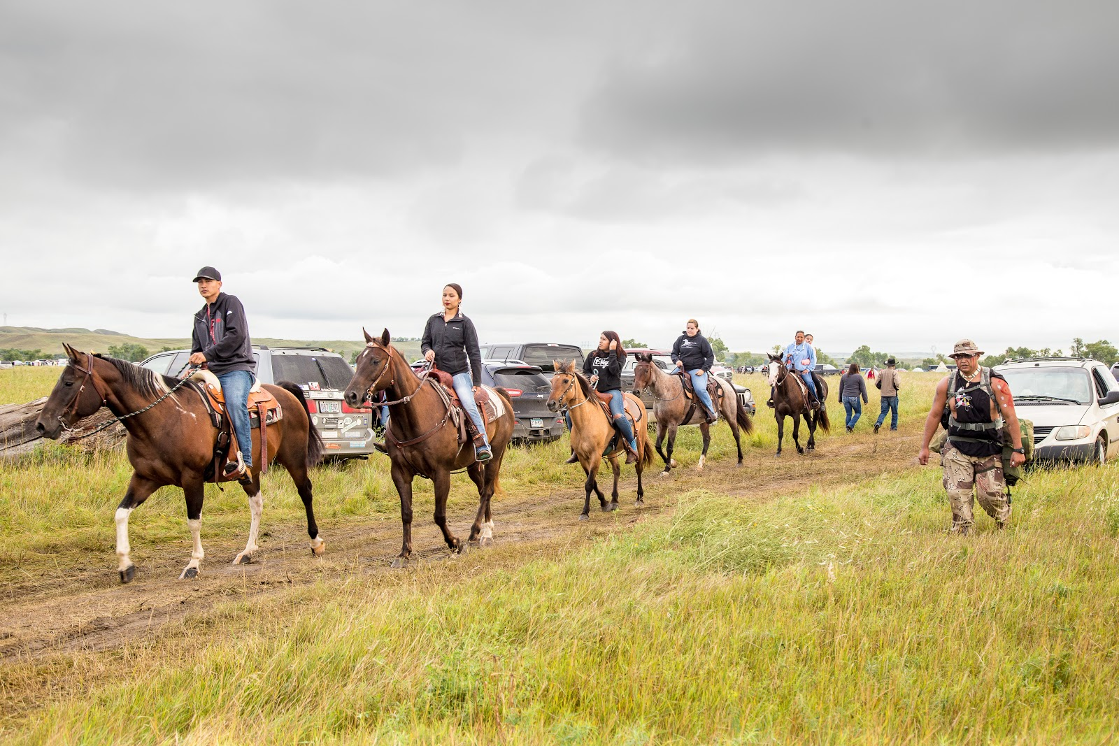 Horses and their riders receive an escort to the water to see the paddlers off. (Photo: Alex Hamer)