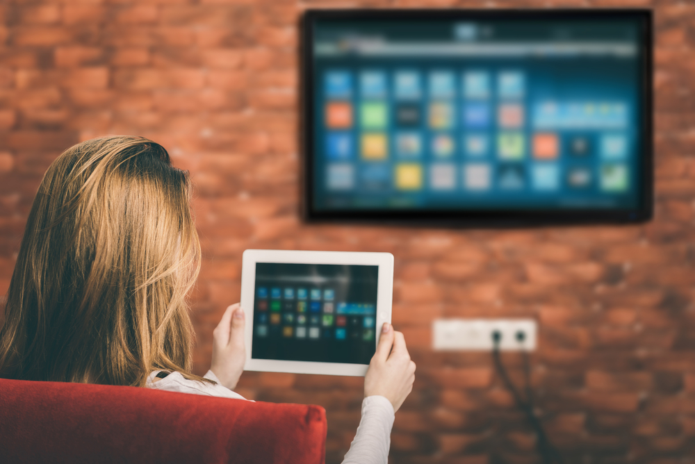 Woman looking at connected TV streaming services on her ipad and TV