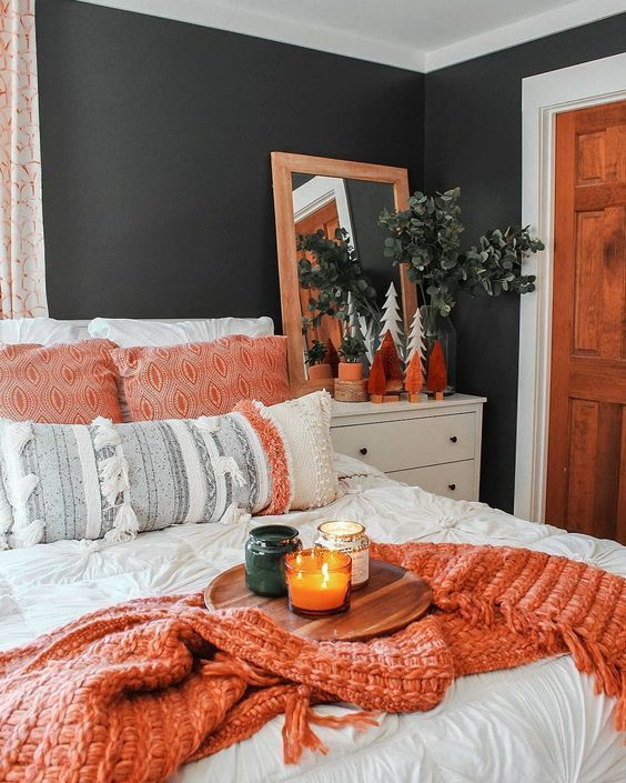 Modern fall decor bedroom setting with orange accents of pillows and blankets and candle.