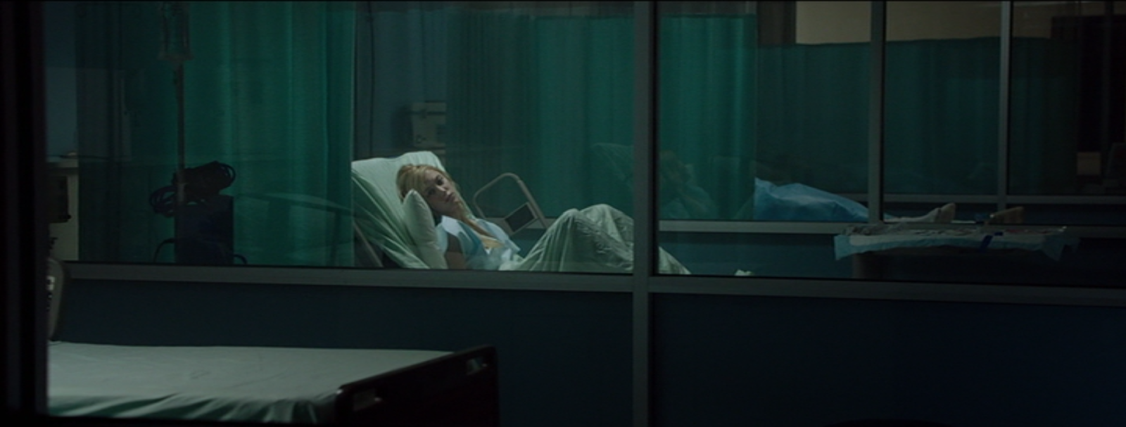 Jay lays in a hospital bed behind a glass partition. The room is darkened and empty.