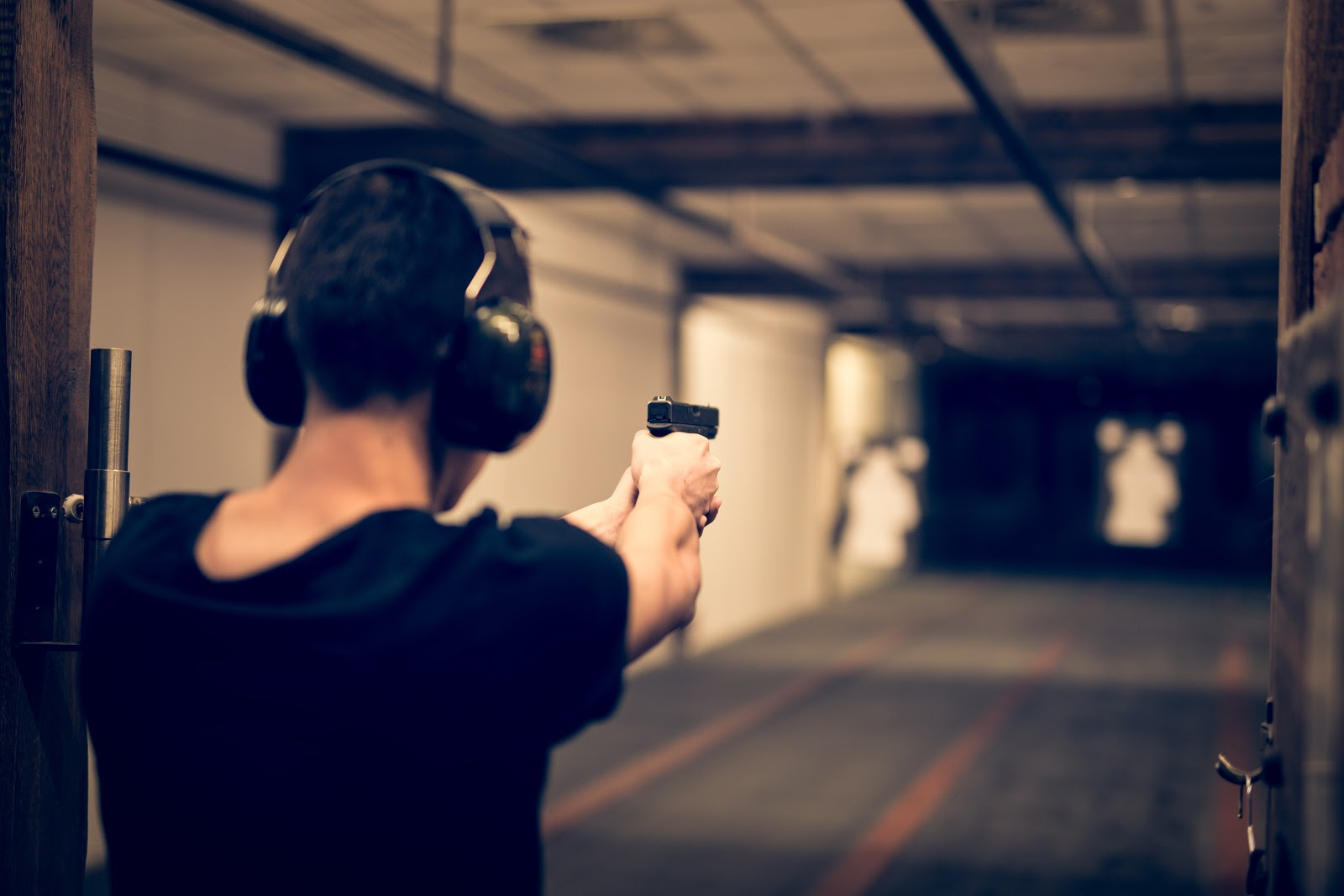 man aiming a pistol downrage at a shooting range with hearing protection