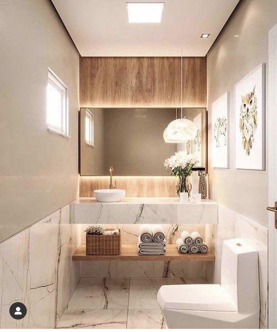 Banheiro com meia parede inferior e pia revestida de porcelanato marmorizado branco, outra metade pintada em tom neutro, revestimento de madeira na parede da pia com espelho retangular com luz de led.