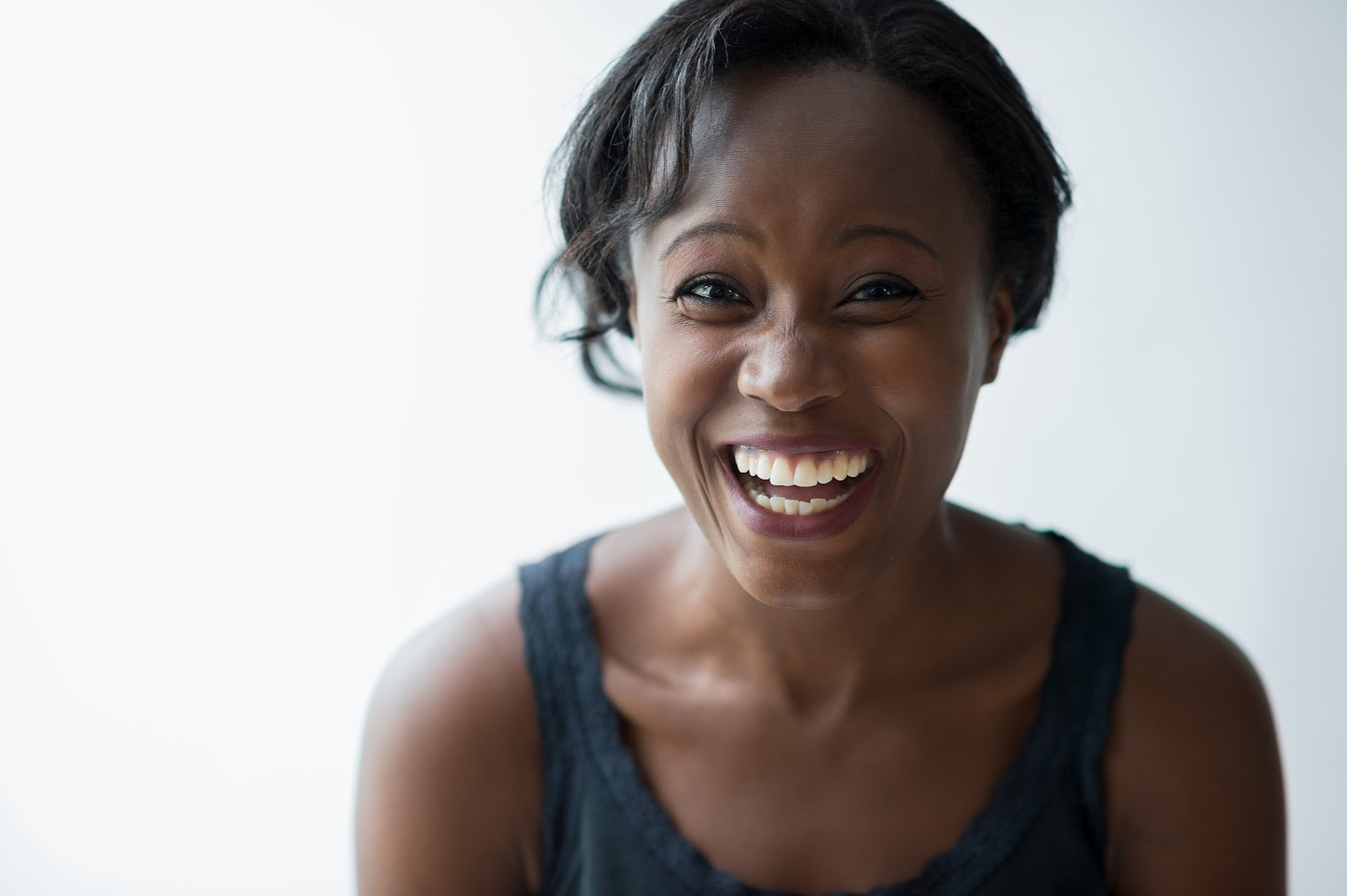 a woman laughs against a white background