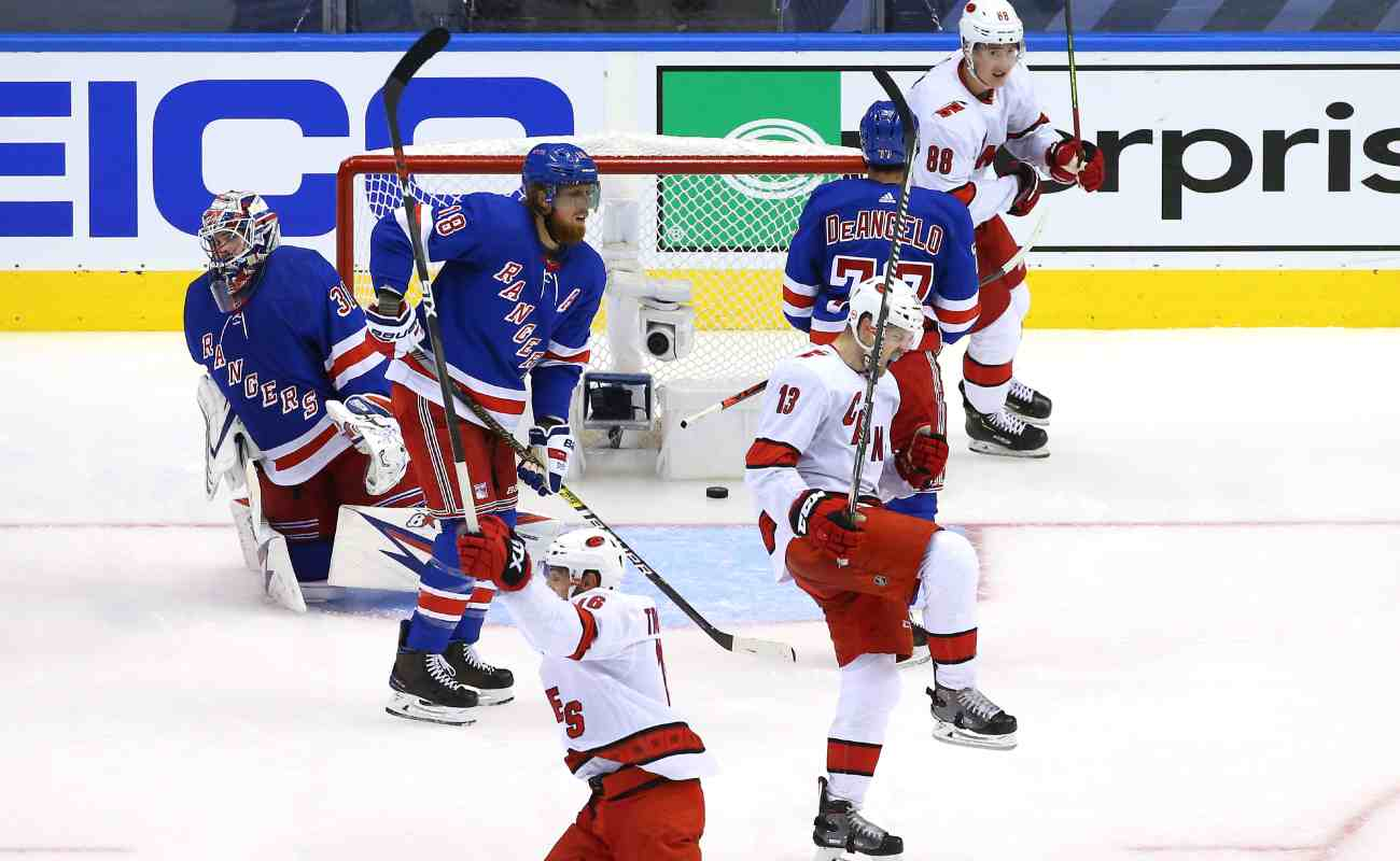Carolina Hurricanes players celebrating after a goal scored by Warren Foegele against the New York Rangers.