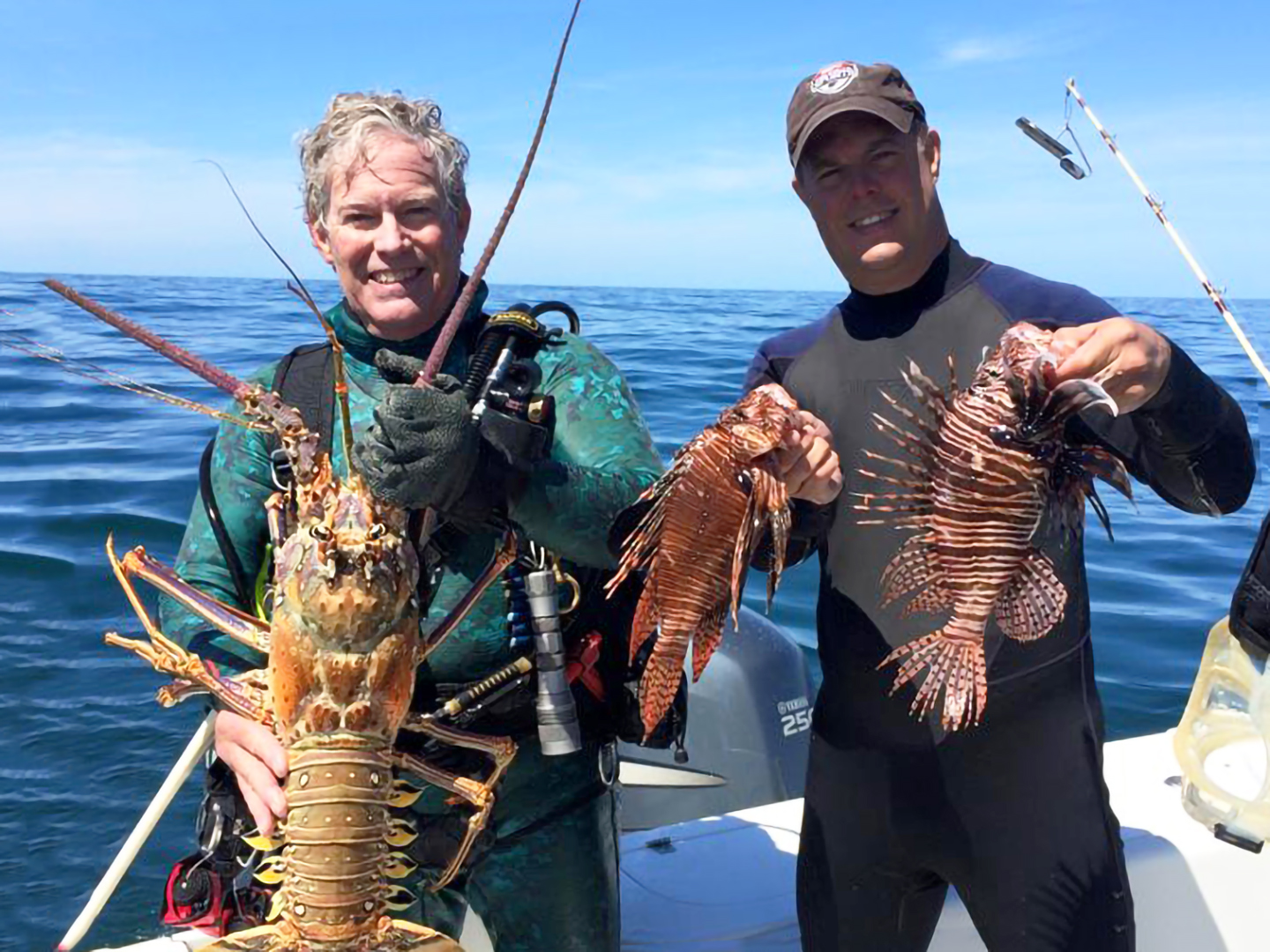 An image of two men holding their catch after spearfishing inclifing a Lobster and Lionfish