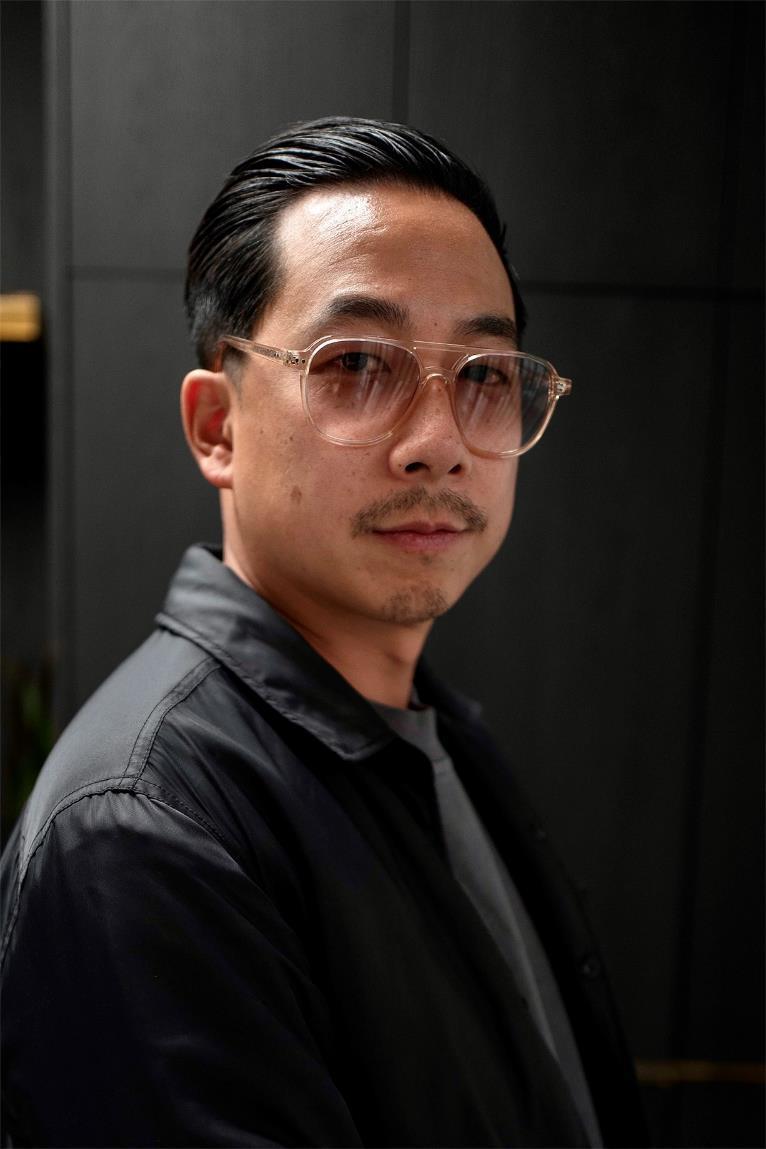 Un hombre con lentes y una camisa negra  Descripción generada automáticamente