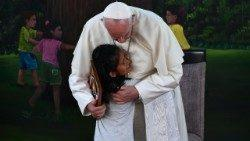 """Pope Francis is hugged by a girl during his visit to """"The Little Prince"""" children's home in Puerto Maldonado"""