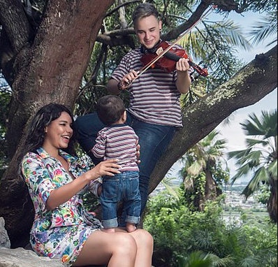 A transgender parent is leaning against a tree and playing the violin for their spouse and child.