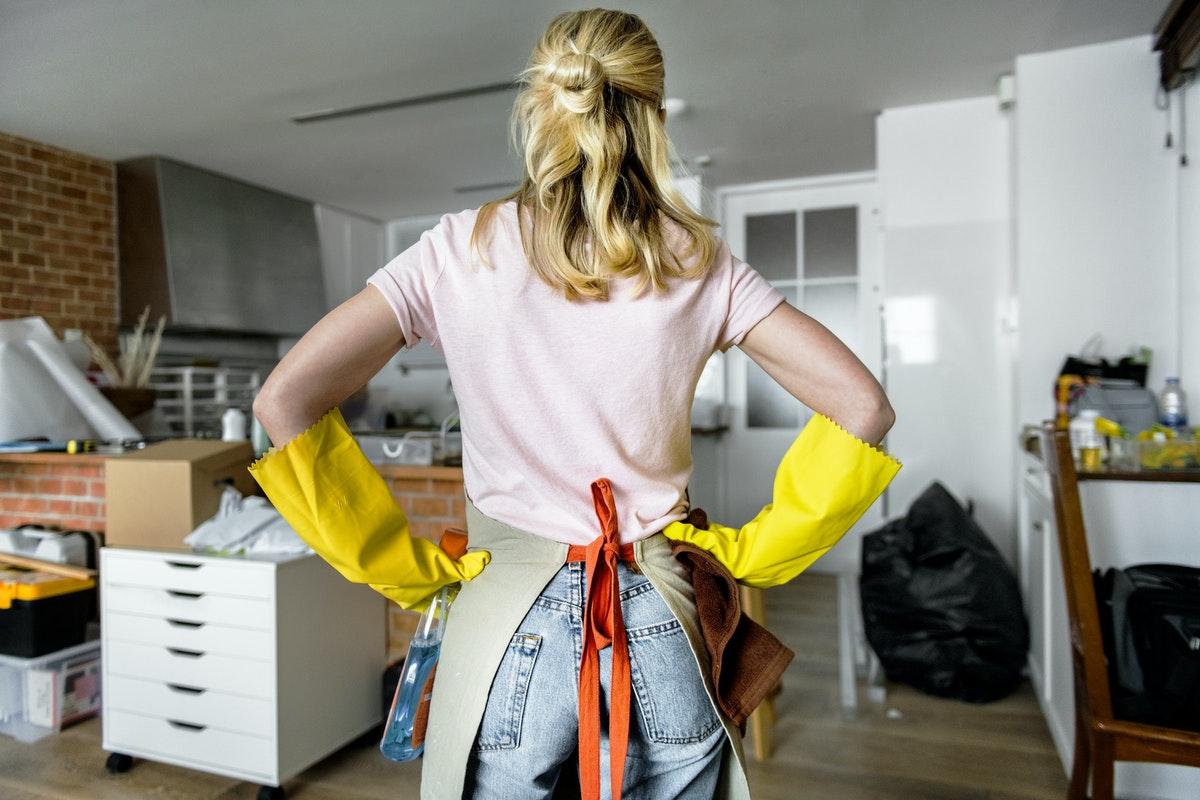 Uma mulher de costas com as mãos na cintura observando um cômodo bagunçado.