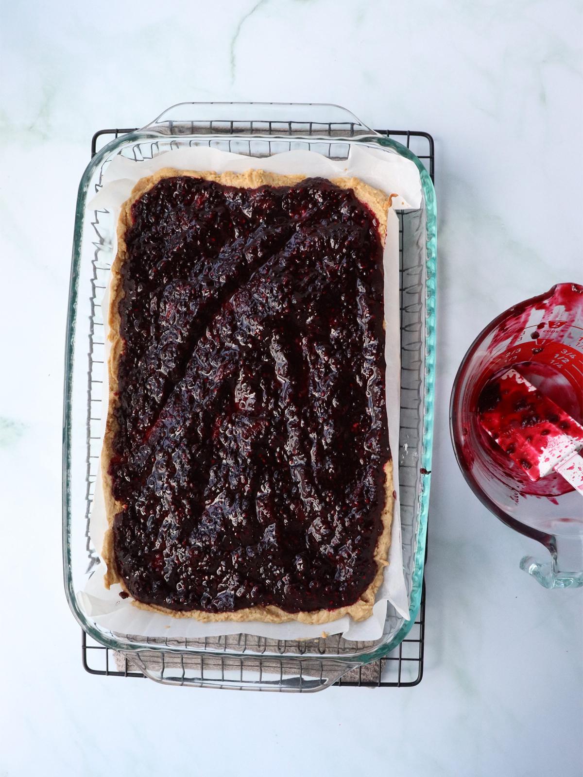 Blackberry jam spread over peanut butter cookie crust