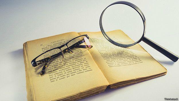 Очки и лупа на старой книге