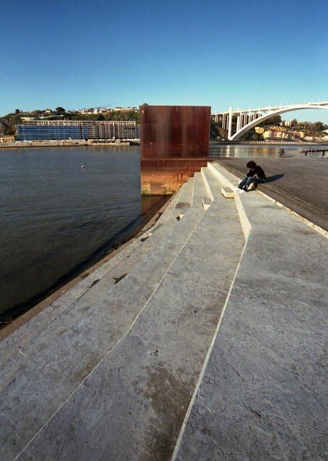 Margem do Rio Douro com uma escultura e a ponte da Arrábida ao fundo.