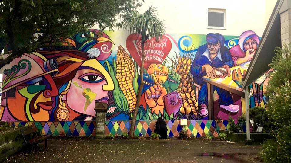 "Latin community mural in Newtown, Wellington, painted by Chilean muralist Alfonso Ruiz Pajarito. Mural integrates Māori and Latin American art motifs, depicting solidarity between workers, indigenous peoples, and ethnic minorities. A heart in the centre contains the text: ""Kotahitanga, community, diversidad."""