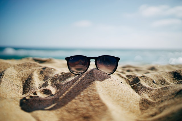 A pair of glasses on the sand of a beach